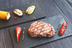 Grilled beef steak closeup on dark wooden table background Stock Photography