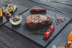 Grilled beef steak closeup on dark wooden table background Royalty Free Stock Photography