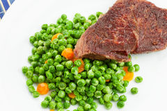 Grilled beef steak with cooked peas Royalty Free Stock Photography