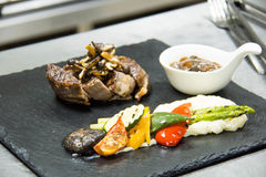 Grilled  beef steak cut  and served on kitchen board garnished. Delicious portion  grilled  beef steak cut  and served on kitchen board garnished with vegtable Stock Image