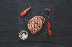 Grilled beef steak on dark wooden table background, top view Stock Image