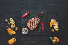 Grilled beef steak on dark wooden table background, top view Royalty Free Stock Photography