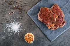 Grilled beef steak fillet with ingredients like sea salt, pepper and onion on black board, food background for restaurant Royalty Free Stock Image