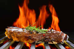 Grilled beef steak. On the flaming grill Royalty Free Stock Photo