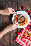 Grilled beef steak with fresh cherry tomato, baked potatoes and red hot chili peppers. Female hands.  Stock Photo