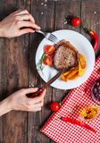 Grilled beef steak with fresh cherry tomato, baked potatoes and red hot chili peppers. Female hands.  Stock Images