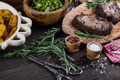Grilled beef steak with fresh herbs and roasted potatoes Royalty Free Stock Photos