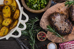 Grilled beef steak with fresh herbs and roasted potatoes Stock Photos