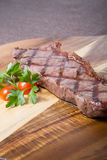 Grilled beef steak. Fresh juicy grilled beef steak on wooden board Royalty Free Stock Image
