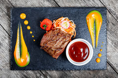Grilled beef steak with fresh salad and bbq sauce on stone slate background on wooden background. Close up. Hot Meat Dishes. Top view stock images