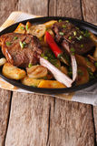 Grilled beef steak with fried potatoes on a plate close-up. vert. Grilled beef steak with fried potatoes on a plate close-up on the table. vertical Stock Photos