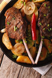 Grilled beef steak with fried potatoes on a plate close-up. vert. Grilled beef steak with fried potatoes on a plate close-up on the table. vertical top view Stock Photo