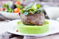 Grilled beef steak, green mashed potatoes with peas, herbs Stock Image