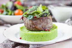 Grilled beef steak, green mashed potatoes with peas, herbs, tast Royalty Free Stock Photo