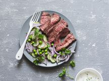 Grilled beef steak and green peas, radish, cucumber salad on a gray background, top view. Healthy food concept Stock Photography