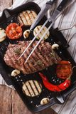 Grilled beef steak on the grill pan closeup, vertical top view Royalty Free Stock Image