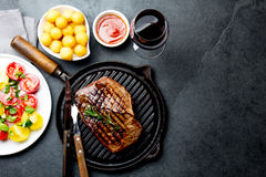 Grilled beef steak on grill pan served with tomato salad, potatoes balls and wine. Barbecue, bbq meat beef tenderloin. Top view, slate background royalty free stock images