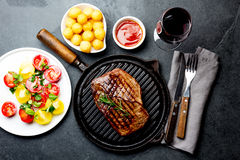 Grilled beef steak on grill pan served with tomato salad, potatoes balls and wine. Barbecue, bbq meat beef tenderloin. Top view, slate background Stock Photography