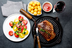 Grilled beef steak on grill pan served with tomato salad, potatoes balls and wine. Barbecue, bbq meat beef tenderloin. Top view, slate background royalty free stock image