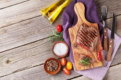 Grilled beef steak. With rosemary, salt and pepper on wooden table. Top view with copy space Royalty Free Stock Photography