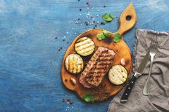 Grilled beef steak, herbs and spices on a blue rustic background. Top view, flat lay.