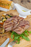 Grilled beef steak macro. Grilled beef steak with vegetables on the wooden plate Stock Images