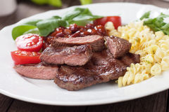 Grilled beef steak. Beef steak with pasta and red kidney beans Stock Images