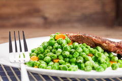 Grilled beef steak with peas and carrot Stock Photos