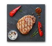 Grilled beef steak and pepprs isolated on white. Grilled beef steak and roasted peppers on slate isolated on white background, top view. Juicy meat with rosemary Stock Photography