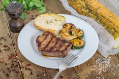 Grilled beef steak on plate. Grilled beef steak with vegetables on the wooden table Royalty Free Stock Photography