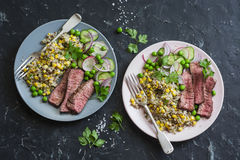 Grilled beef steak and quinoa corn mexican salad on dark background, top view. Delicious healthy balanced food stock photography