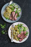 Grilled beef steak and quinoa corn salad on dark background, top view royalty free stock images