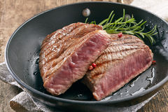 Grilled beef steak. With rosemary on frying pan Royalty Free Stock Image
