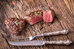 Grilled beef steak with rosemary, salt and pepper on old cutting board. Beef Stock Photos