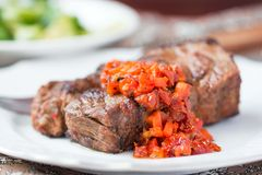 Grilled beef steak with salsa sauce dried tomatoes, red peppers Royalty Free Stock Photos