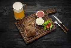 Grilled beef steak with sauces and beer mug on a board. Dark wooden table. Stock Photos