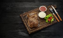 Grilled beef steak with sauces on a board. Dark wooden table. Royalty Free Stock Images