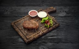 Grilled beef steak with sauces on a board. Dark wooden table. Grilled beef steak with sauces on a board Stock Images