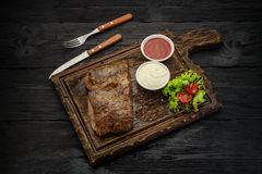 Grilled beef steak with sauces on a board. Dark wooden table. Royalty Free Stock Image