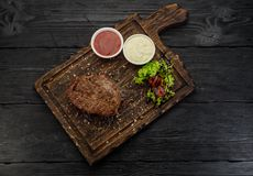 Grilled beef steak with sauces on a board. Dark wooden table. Grilled beef steak with sauces on a board Stock Photography