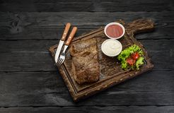 Grilled beef steak with sauces on a board. Dark wooden table. Grilled beef steak with sauces on a board Stock Image