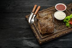 Grilled beef steak with sauces on a board. Dark wooden table. Grilled beef steak with sauces on a board Royalty Free Stock Photography
