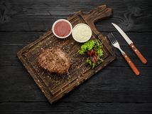 Grilled beef steak with sauces on a board. Dark wooden table. Stock Photography