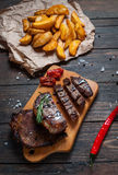 Grilled beef steak seasoned with spices served on a wooden board with baked potatoes and red hot chili peppers.  Stock Photo