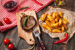 Grilled beef steak seasoned with spices served on a wooden board with fresh cherry tomato, baked potatoes and red hot chili pepper Stock Images