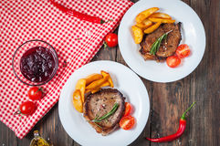 Grilled beef steak seasoned with spices served on a wooden board with fresh cherry tomato, baked potatoes and red hot chili pepper. S Stock Photography
