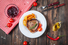 Grilled beef steak seasoned with spices served on a wooden board with fresh cherry tomato, baked potatoes and red hot chili pepper Stock Image
