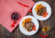 Grilled beef steak seasoned with spices served on a wooden board with fresh cherry tomato, baked potatoes and red hot chili pepper. S Royalty Free Stock Photos