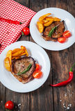 Grilled beef steak seasoned with spices served on a wooden board with fresh cherry tomato, baked potatoes and red hot chili pepper. S Royalty Free Stock Images