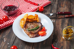 Grilled beef steak seasoned with spices served on a wooden board with fresh cherry tomato, baked potatoes and red hot chili pepper. S Royalty Free Stock Photo